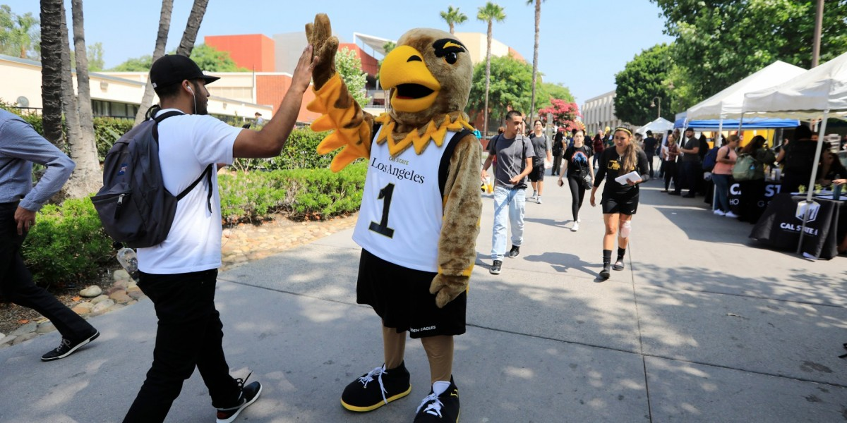 Eddie the Golden Eagle high-fiving a student on the Main Walkway.