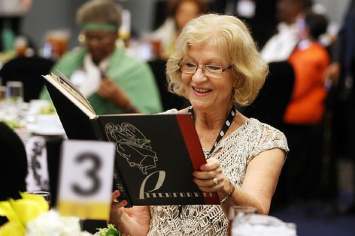 Female alumna opening a yearbook at a reception table