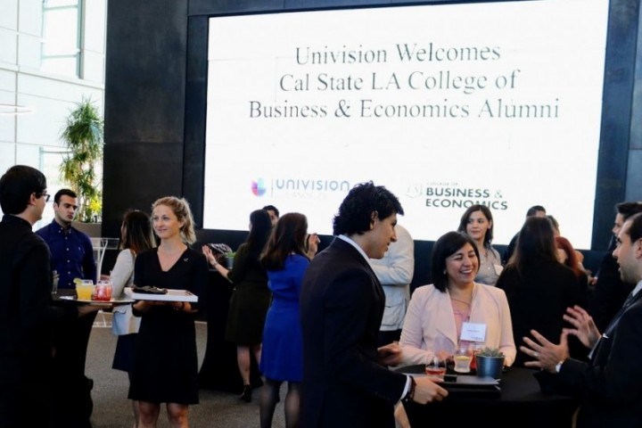 People networking around cocktail tables with Univision welcome sign