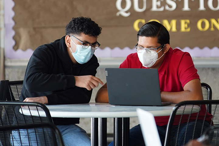 Two male students looking at a laptop at the library