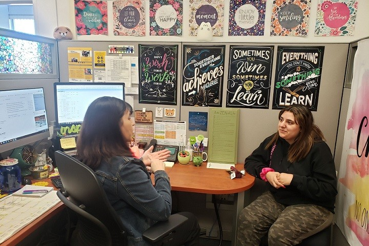 Two women sitting down facing each other and talking. Behind are posters and two computer screens