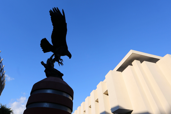 Eagle statue and white building behind. Backdrop is a blue sky