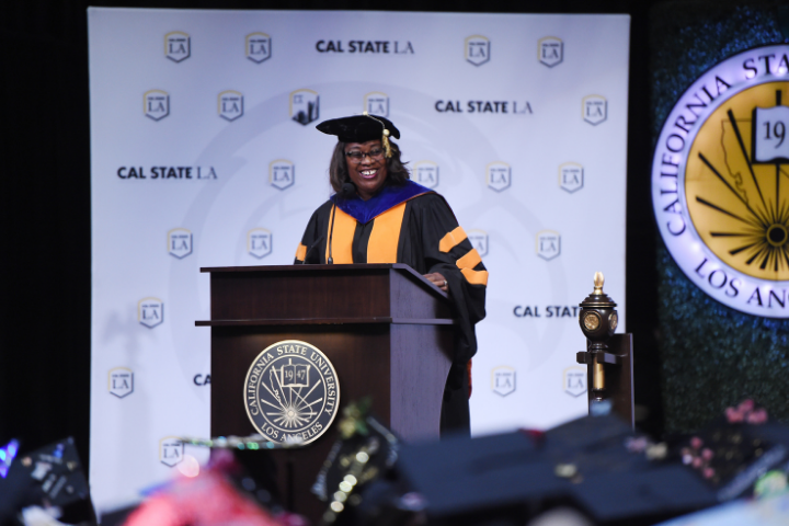 Black woman in regalia standing on a podium in front of Cal State La banner