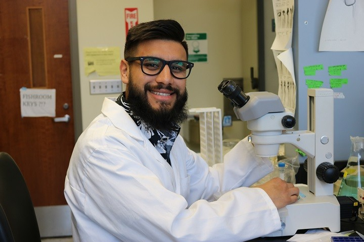 male student with a beard, glasses and white lab coat smiling at the camera. He is holding a microscope in a lab