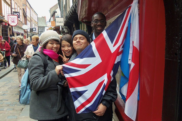 Three students holding a UK flag
