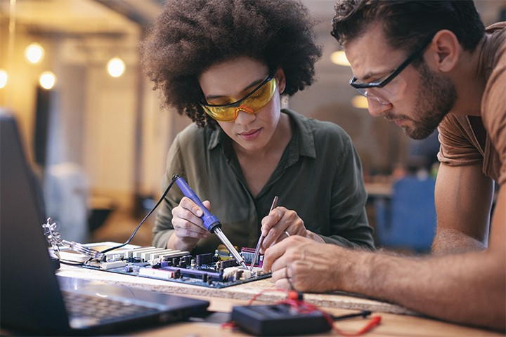 Female and male electrical engineers working on circuit board