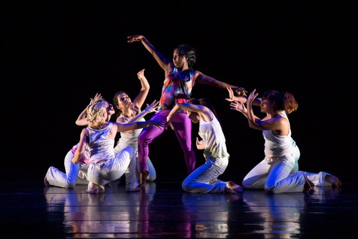 A group of dancers, dressed in white, create an ensemble shape in dramatic lighting.