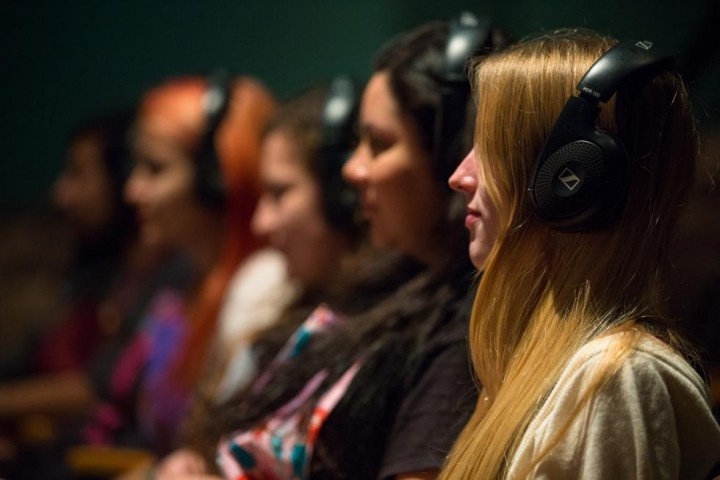 A seated row of students in an audio production class, each wearing headphones.