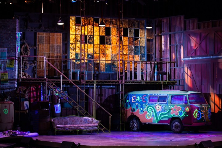 A wide shot of a past production of Hair, complete with Volkswagen bus onstage.