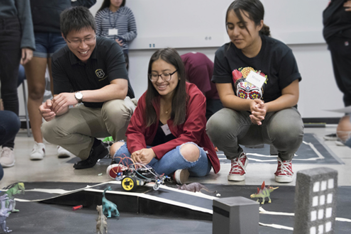 ecst faculty and two girls watch vehicle race on city mockup