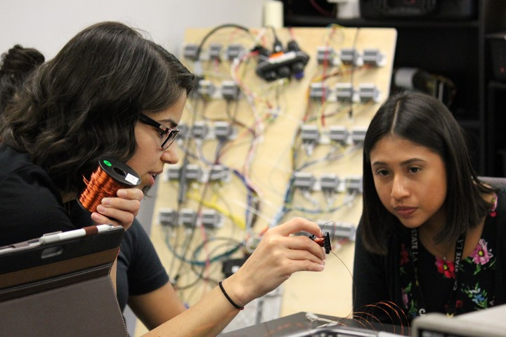 female ECST student facilitator hold wire and explains to student