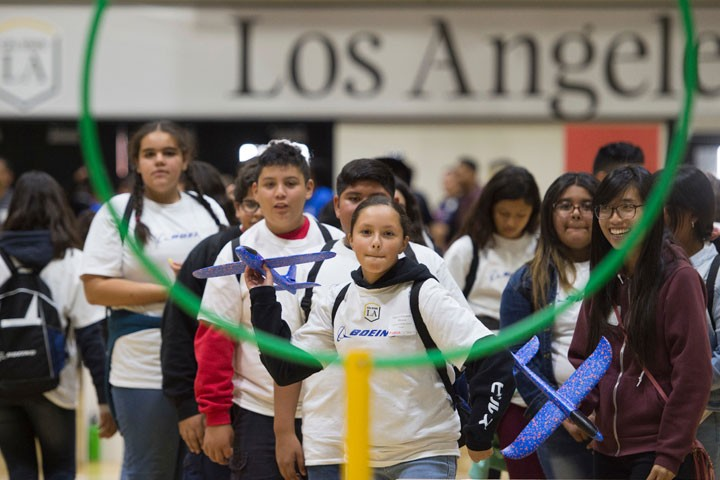 young girl aims to throw airplane through hoop on ecst open house