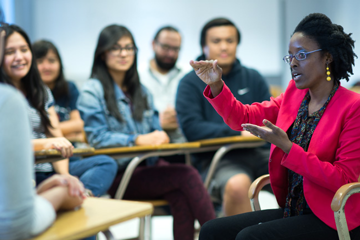 female advisor speaks to seated students in classroom