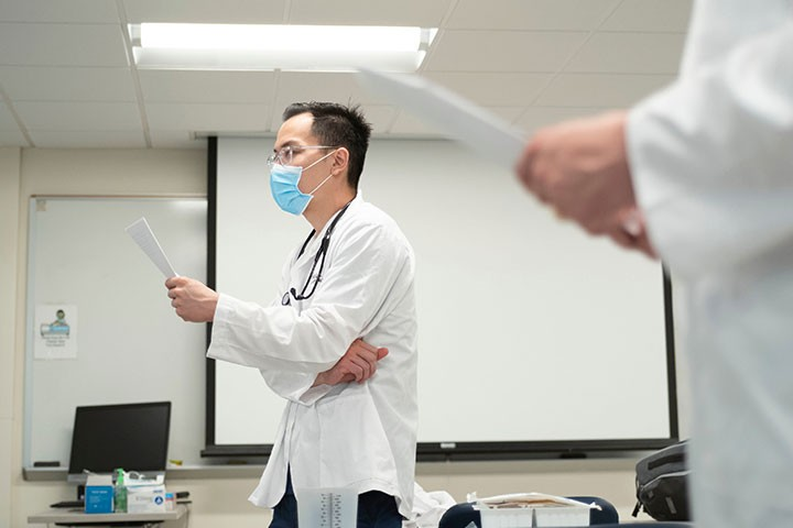 Person in labcoat wearing a mask holding a piece of paper