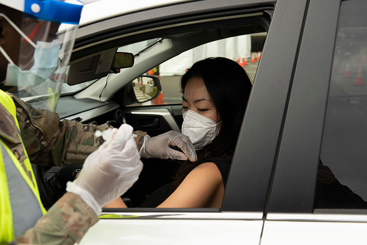 Person wearing a mask getting vaccinated