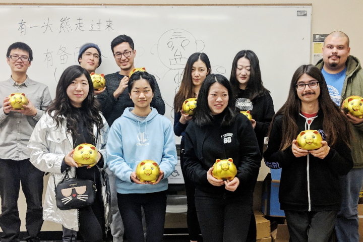Group of students holding gold item in a classroom