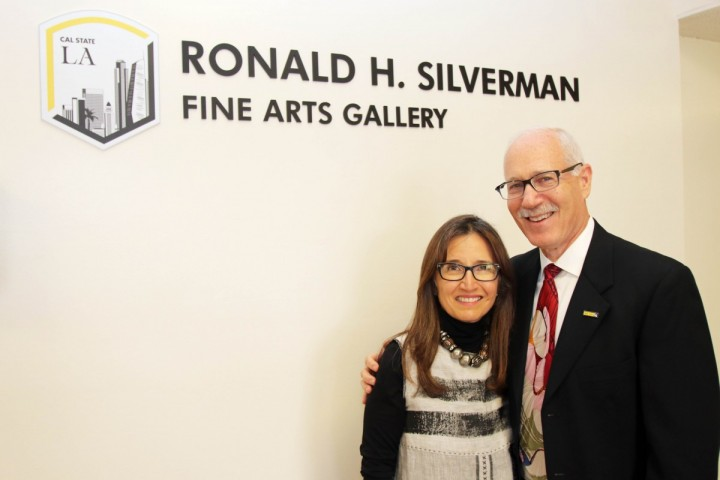 Two people smiling while standing in front of the Ronald H. Silverman Fine Arts Gallery