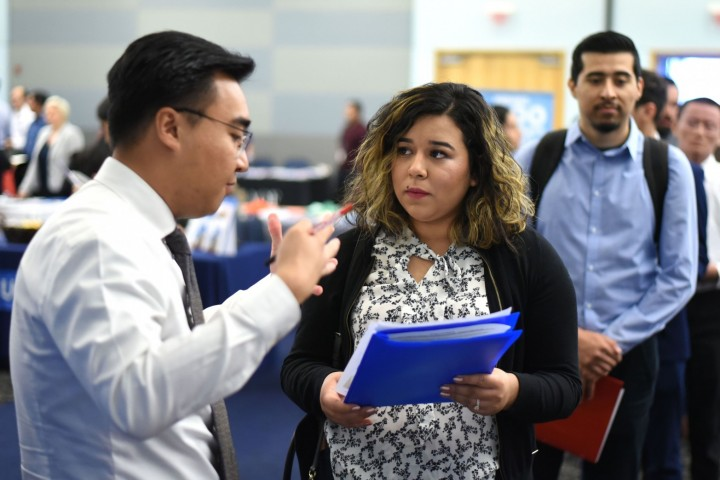 Student holding a portfolio speaks with employer at the career fair.