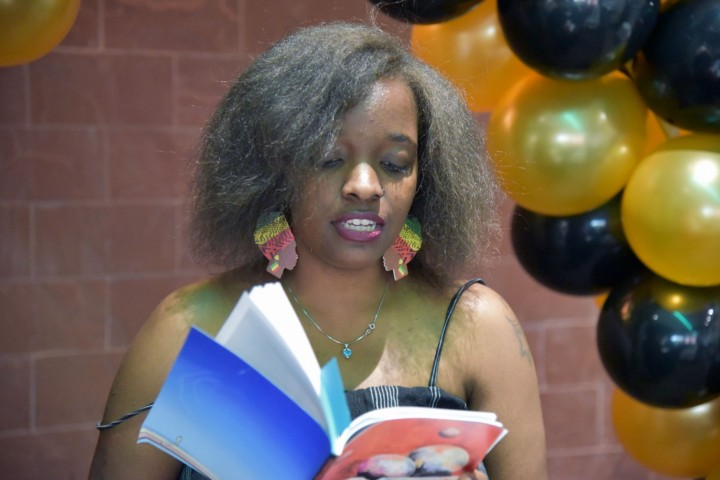 Student reading from a book at an event, balloons in the background.