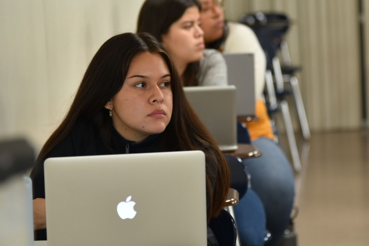 In the foreground, a student sits with an open MacBook. Two more students sit behind her.