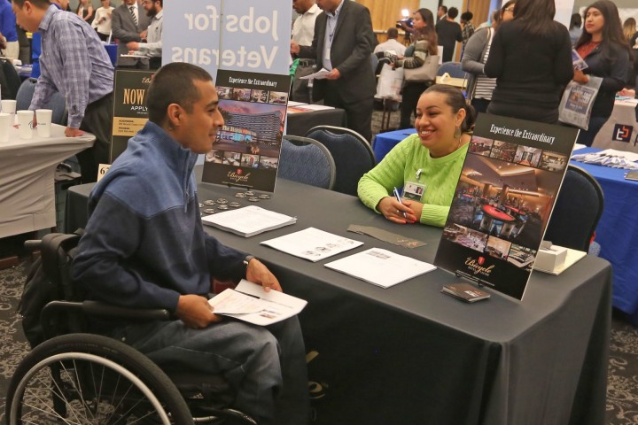 Student in a wheel chair speaking to employer at a career fair.