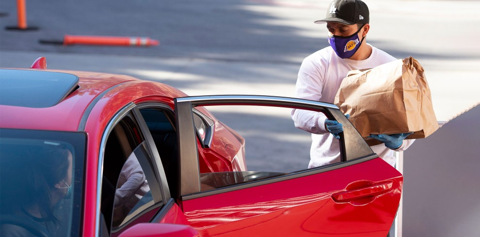 Person in mask gives bag of groceries to person in red car