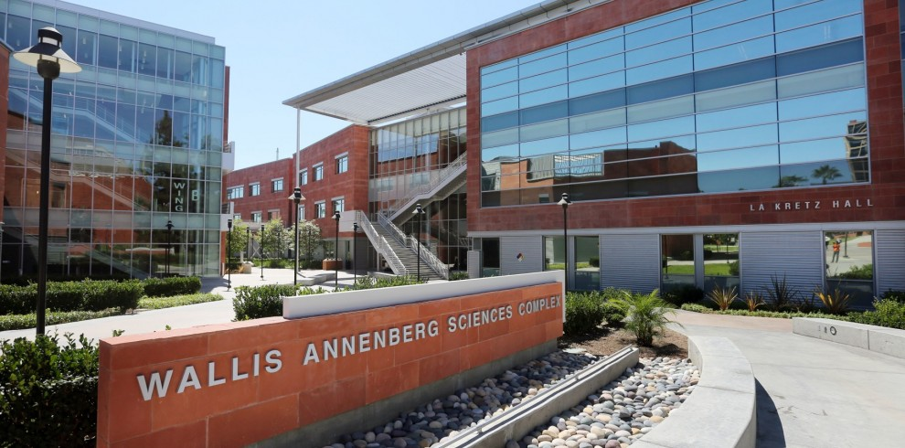 """Two buildings and a courtyard between them. Red brick in front of the courtyard reads """"Wallis Annenberg Science Complex."""""""