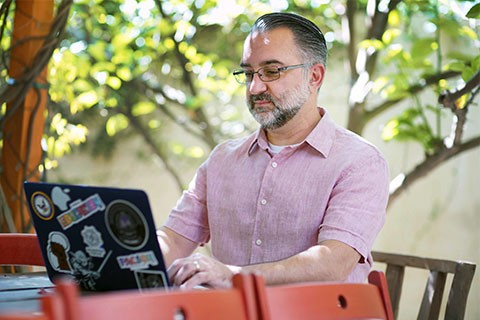 Ali Tayyeb works outside on his laptop