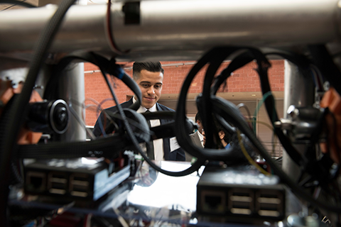 A Cal State LA student is behind an engineering project displayed at a senior design expo.