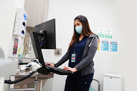 Jessica Schmidt inputting data into a computer at the Via Care Community Health Center.