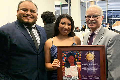 Cal State LA President William A. Covino holds framed award with a student and alumnus