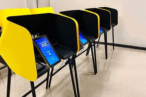 Gold and blue voting machines with a tablet displaying 2020