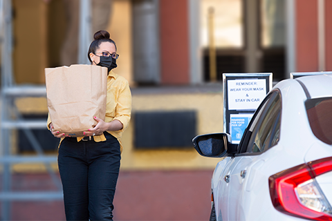 Staff member carries bag of groceries out to a student waiting in a car