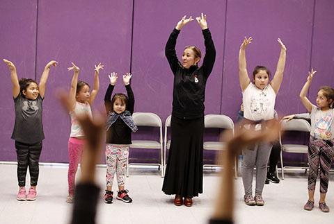 A dance instructor lifts up her hands to demonstrate a dance move to a group of children in a purple room.