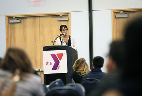 Sandy Banks speaks at a lectern with the Y logo