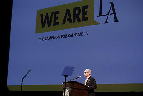 President William A. Covino delivers a speech at a lectern in front of a screen reading We Are LA: The Campaign for Cal State LA