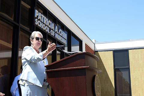 Patricia A. Chin stands at a lectern and speaks during the dedication of the Patricia A. Chin School of Nursing.