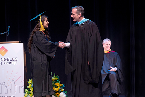 Mayor Garcetti shakes the hand of a student in a cap and gown onstage