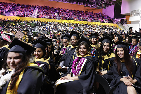 Graduating students seated in the gym during Commencement
