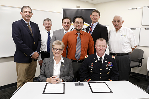 Dean Allen and Col. Gibbs along with representatives during an MOU signing ceremony.