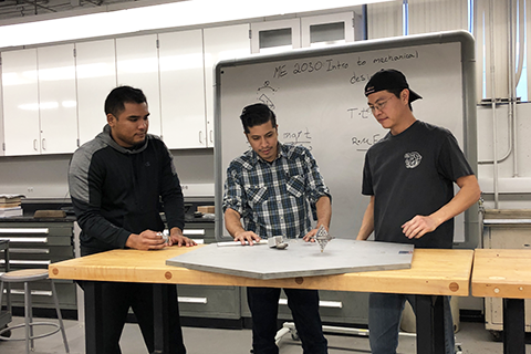 Students designing a gyroscope in engineering lab.