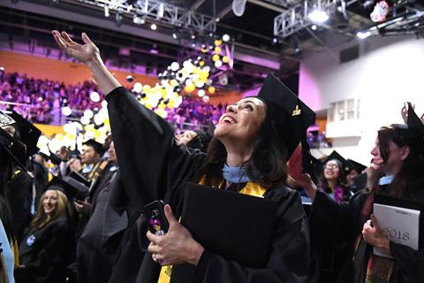 Cal State LA graduate gazes upward as balloons fall in the University Gymnasium