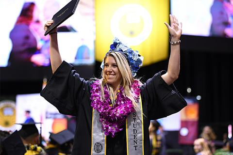 A graduate celebrates as she walks away from the Commencement stage.