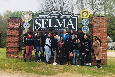 Group of students, staff and faculty on trip in front of sign