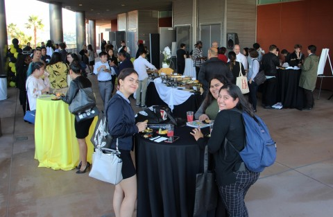 Students smiling for the camera at the networking reception on the Golden Eagle Ballroom patio.