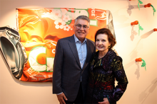 Richard Cordova and Billie Milam Weisman stand in front of art piece that depicts a crushed can of Orange Crush soda