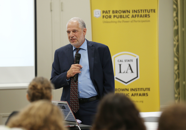 Raphael J. Sonenshein Speaks into a microphone in front of crowd and gold PBI banner