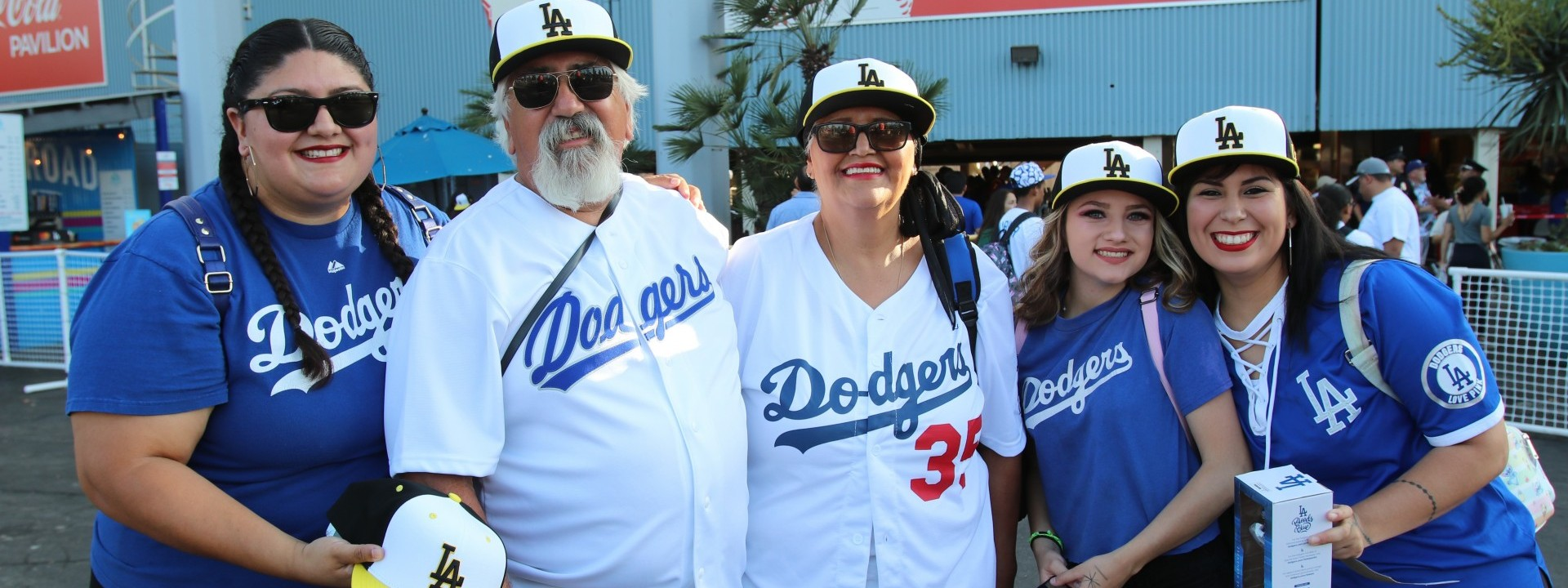 Five people posing with Cal State LA baseball caps at Dodger Stadium
