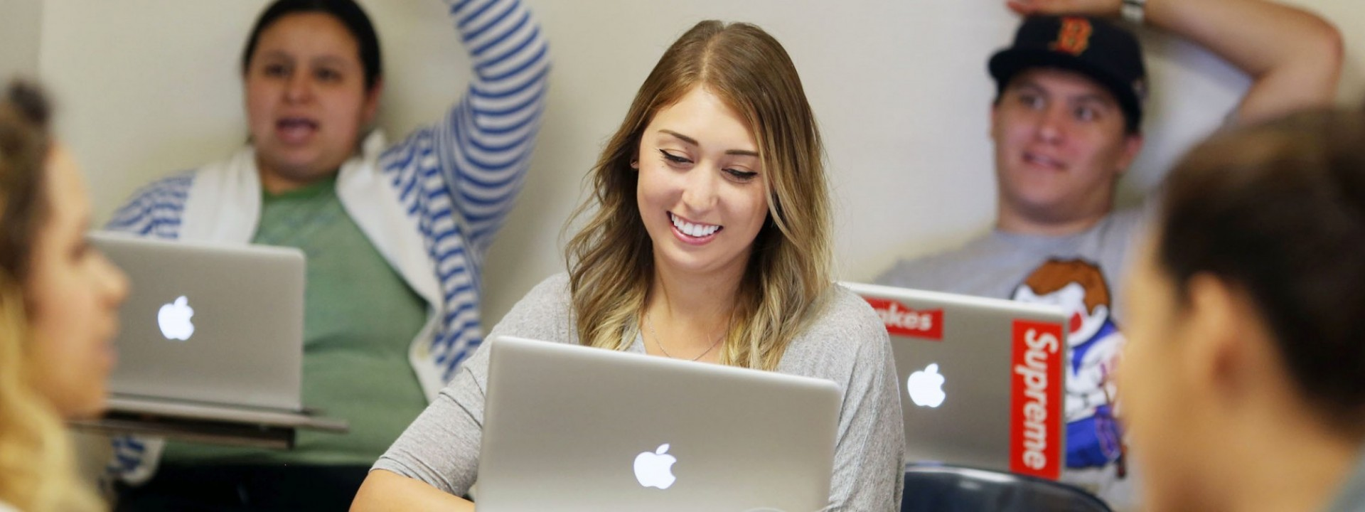 Image of a Caucasian female student smiling in a classroom setting in front of an open laptop.