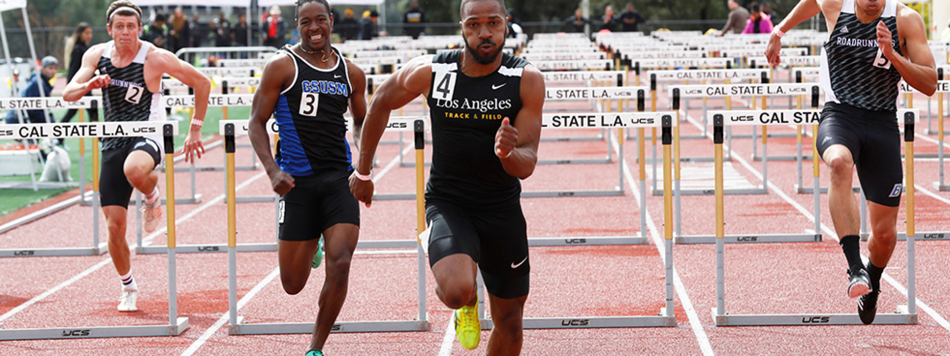 Image of a Cal State LA track star leading a hurdle race.